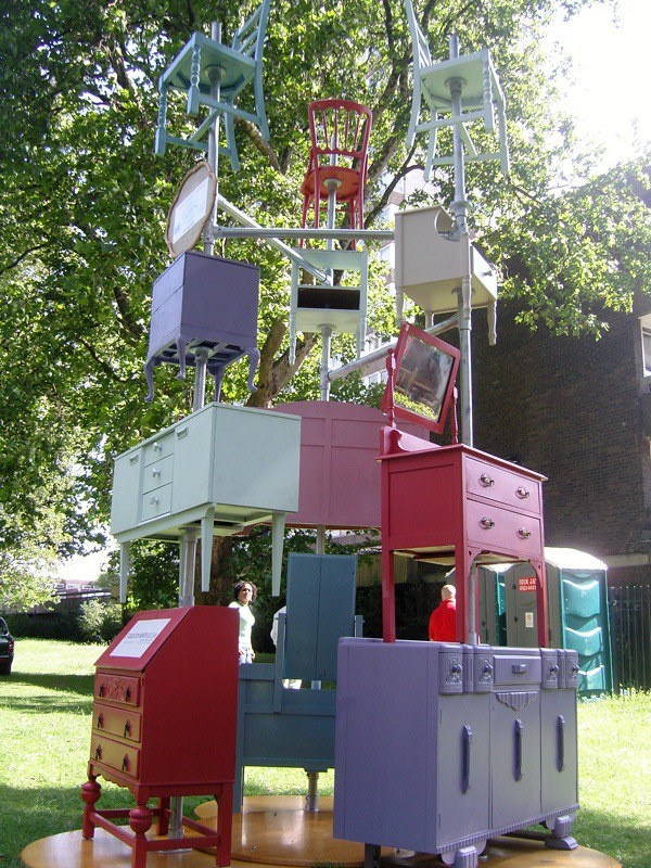 Colorfully painted dressers, chairs, and other furniture stacked in a tower