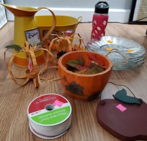 Items found at thrift store including ribbon, plates, pumpkin decor, wooden apple wall decore