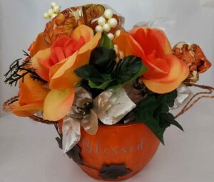 """Pumpkin Bowl with the word """"Blessed"""" filled with orange and champagne flowers"""