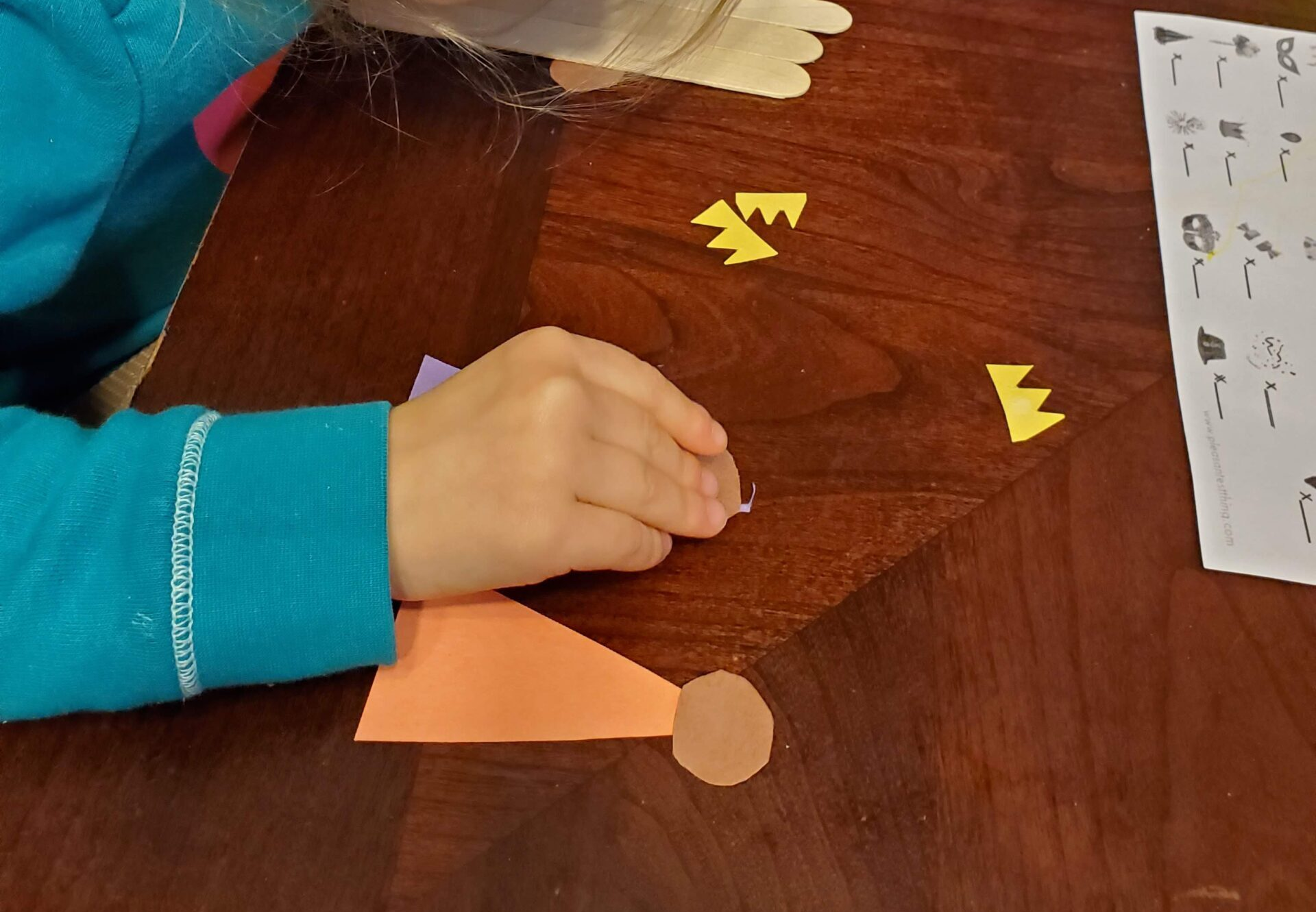 Child creating a construction paper king