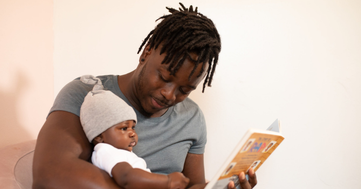Man in gray shirt reading a board book to a baby in a white onesie and hat.