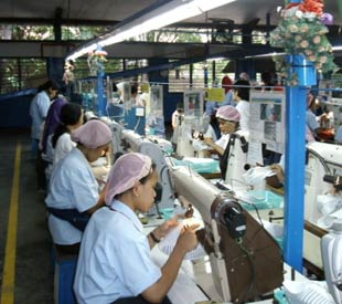 Rows of women wearing matching shirts and hair nets working in a textile sweatshop