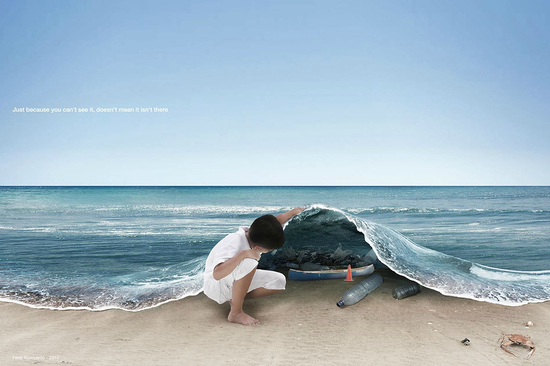 Individual lifting the ocean along the shoreline to reveal plastic pollution, much like lifting a blanket.