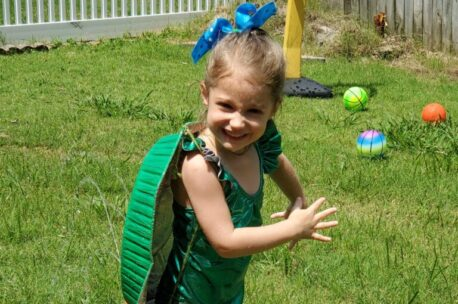 """Smiling, young, white child in green bathing suit with green roaster pan """"turtle shell"""" on her back."""