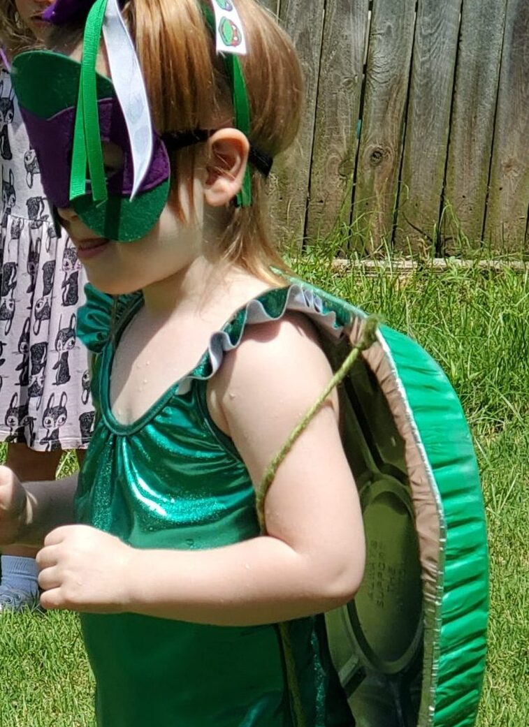 Young white child wearing TMNT mask and roaster pan turtle shell on her back.