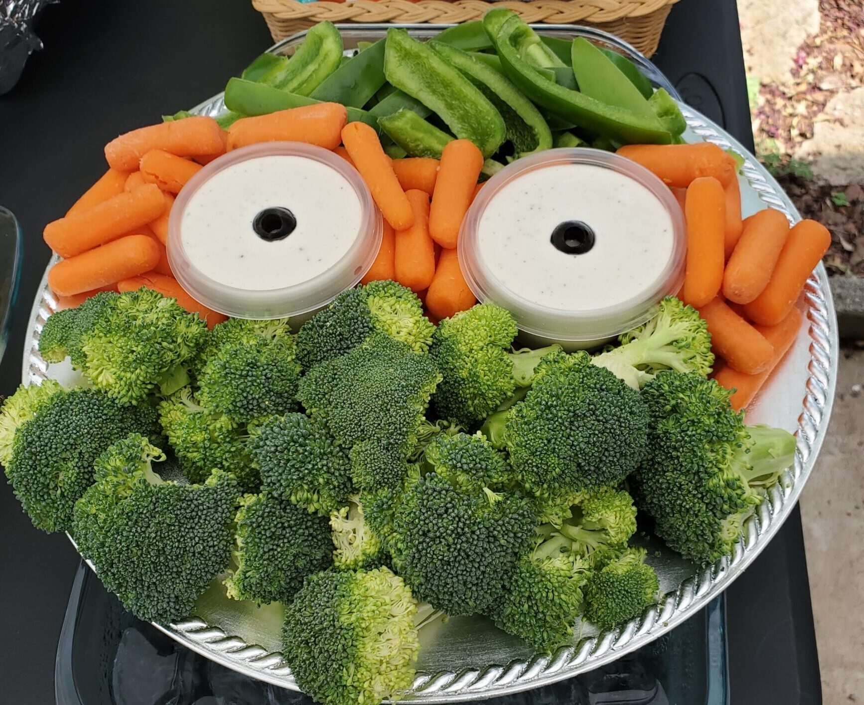 A seasonal, eco-friendly party food: A Veggie Tray made to look like Michelangelo with Broccoli and Green Peppers for the face, carrots for the mask, and cups of dip with olives for the eyes.