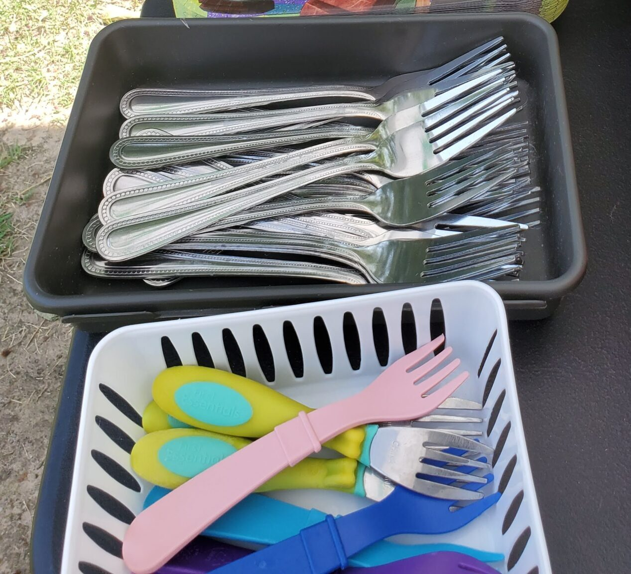 Regular silverware forks in a tray for adults and reusable child forks in another tray for kids.