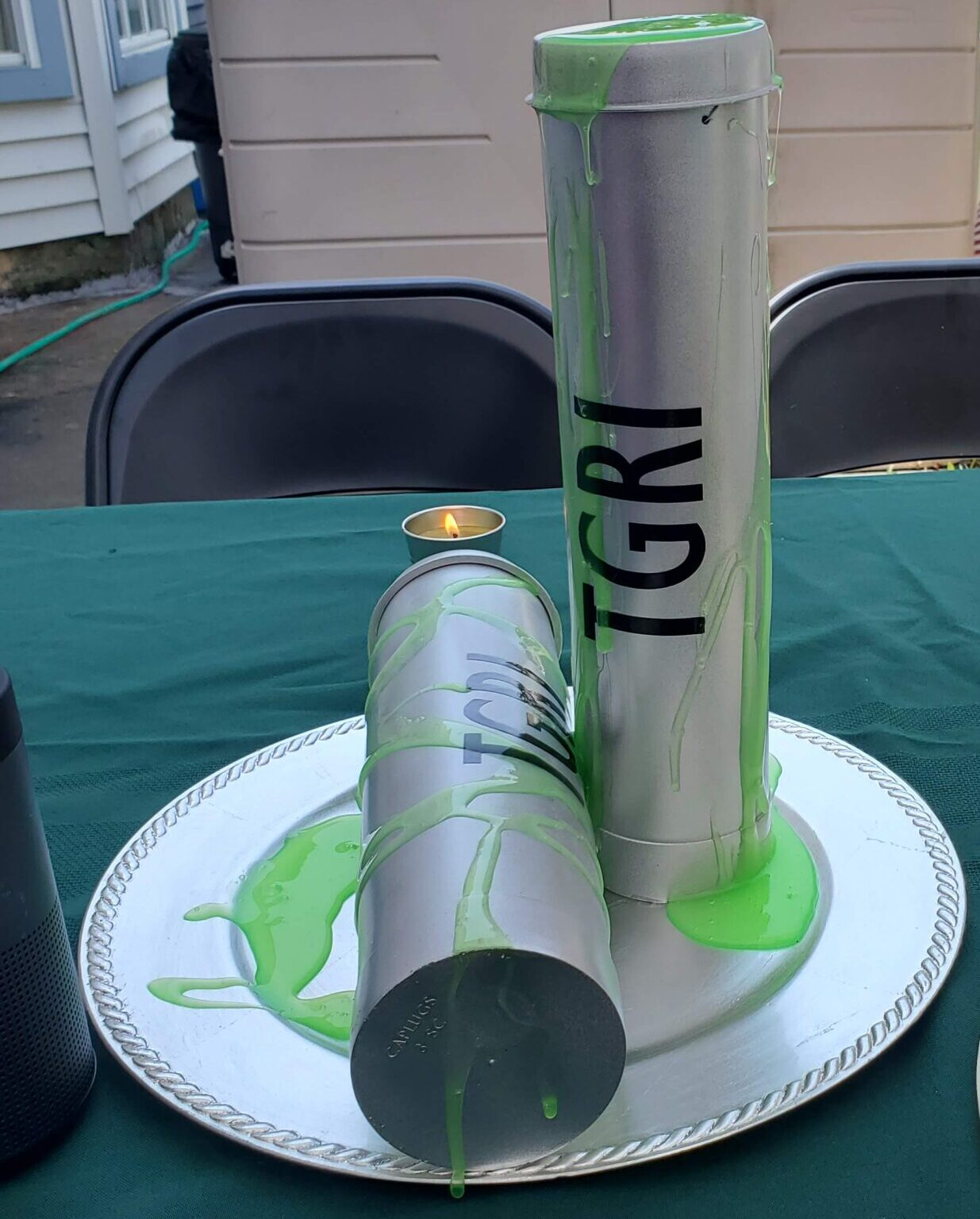 DIY Ooze Cannisters on a table with a dark green fabric table cloth.