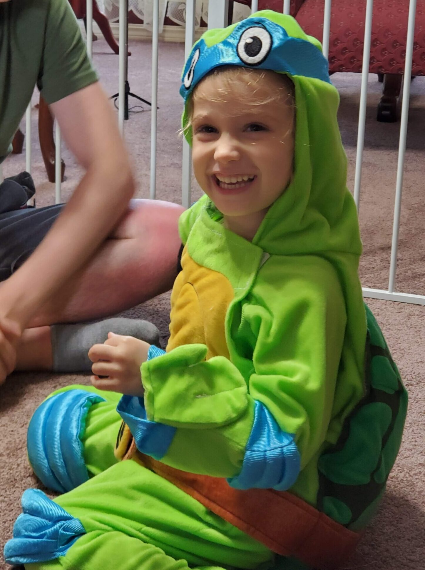 Little white child dressed in a full Leonardo costume with hood. Face is exposed.