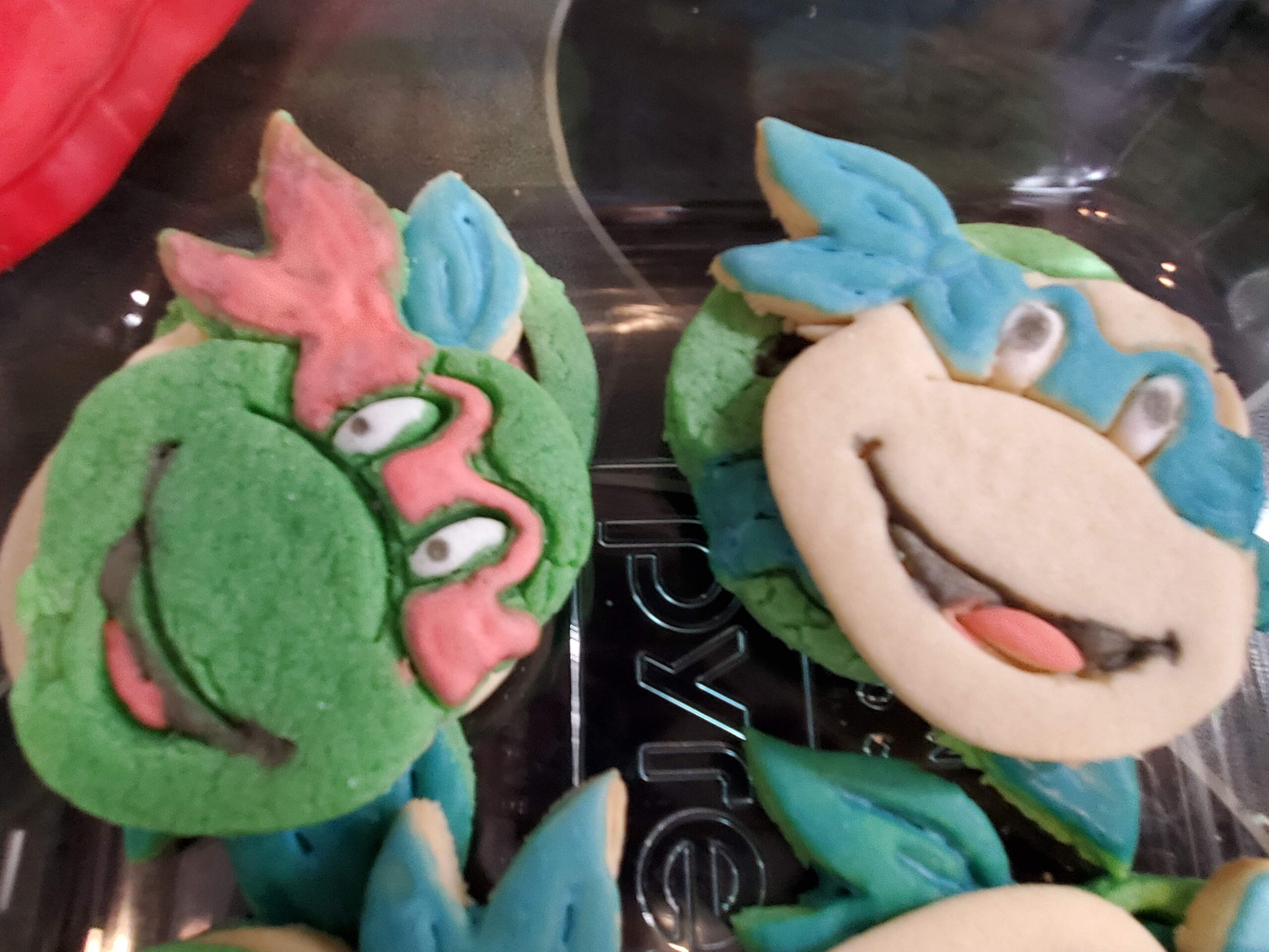 Cookies decorated to look like ninja turtle heads. One is made from green dough and painted with a red mask. Another is untinted dough with a blue mask.