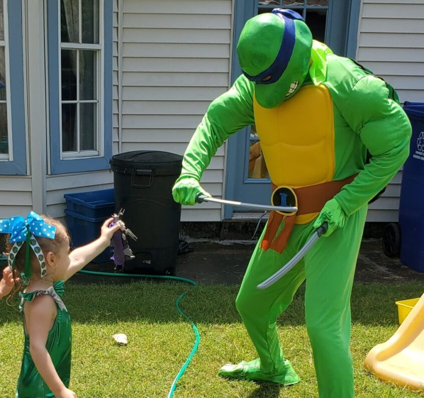 TMNT Character Lenoardo visits and young child holds a figurine of shredder up toward him.