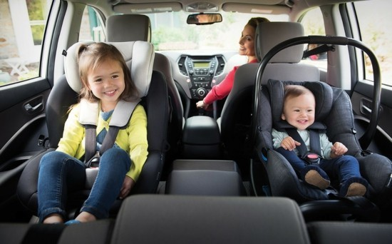 1 toddler and 1 infant in rear-facing carseats in a vehicle with mom turning head to look back at them